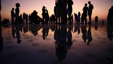 Image of a group of people standing on wet sand