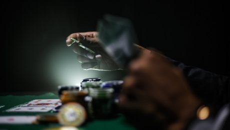 An image of hands holding cards over a table with gambling chips